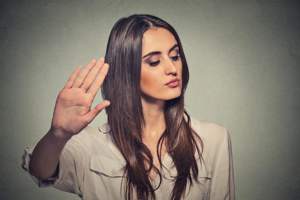 Closeup portrait young annoyed angry woman with bad attitude giving talk to hand gesture with palm outward isolated grey wall background. Negative human emotion face expression feeling body language.jpeg